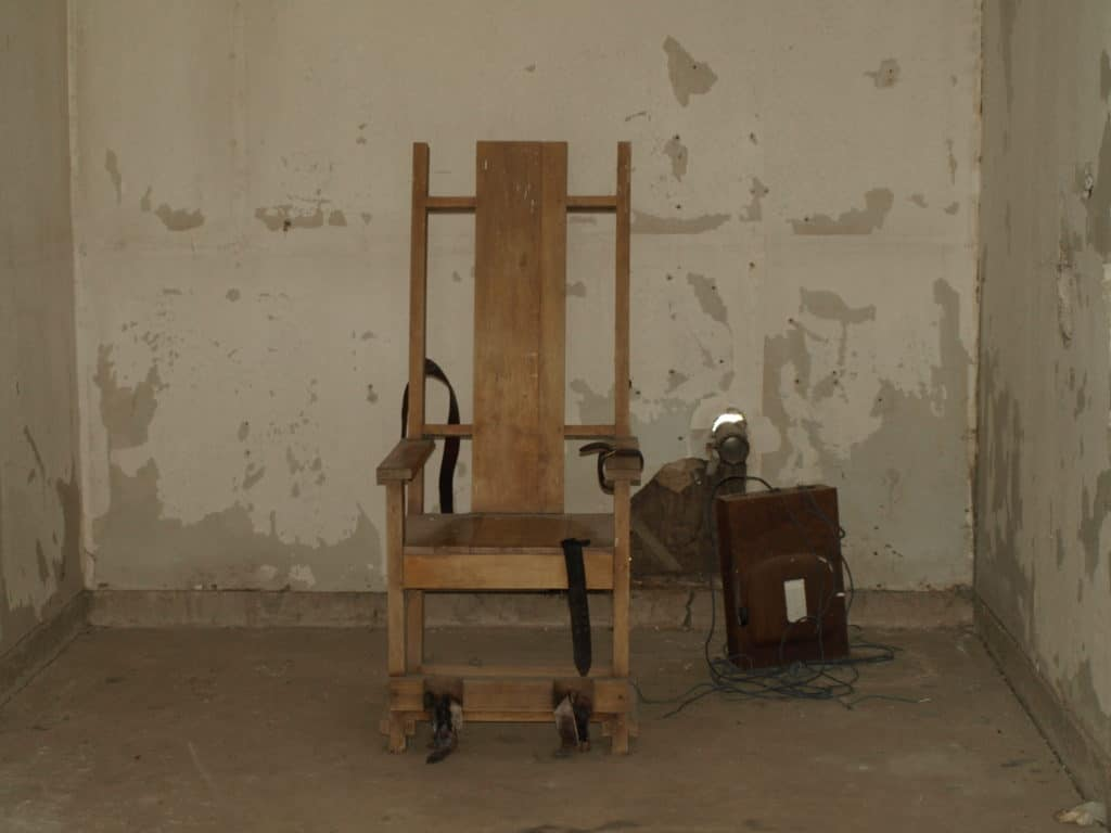 Original Death Chamber at the Red Hat Cell Block. The chair is a replica of the original. The Red Hat was closed in the early 1970s. Photo taken 28 March 2010 by Lee Honeycutt from Angola, LA, USA. (CC BY-SA 2.0).