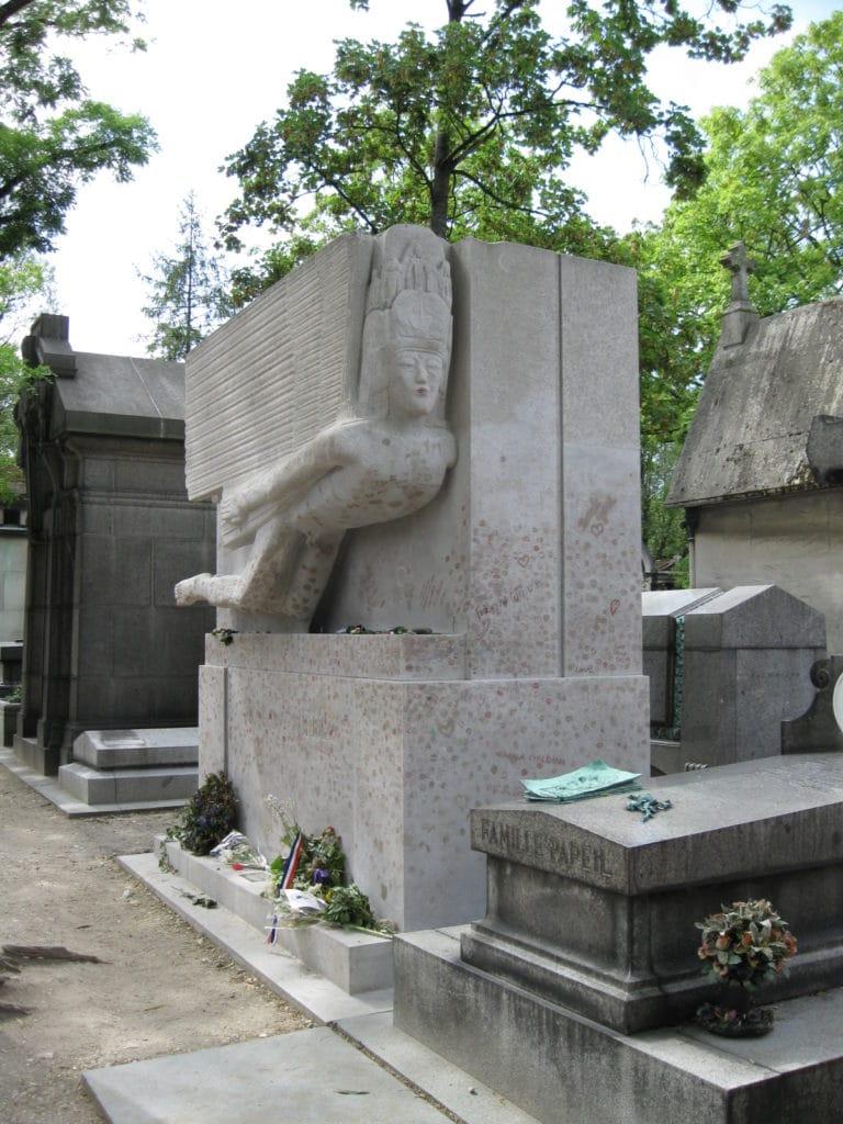 Monumentet (af John Epstein) over Wildes grav på Père Lachaise-kirkegården i Paris er et kultsted med blomster,, symbolske småting og pletterne på monumentet er aftryk af læbestiftskys!! Der er nu en glasmur omkring for at forhindre vandalisering, som fx fjernelse af kønsdele på Epsteins originale monument. Photo from July 29th, 2009 by JHvW (talk). (CC BY-SA 3.0).