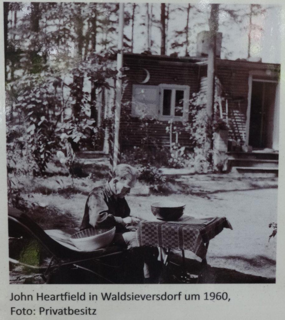 John Heartfield vor seinem Sommerhaus um 1960, Aufnahme auf einer öffentlich zugänglichen Informationstafel vor seinem Sommerhaus in Waldsieversdorf. Photo: Assenmacher. (CC BY-SA 4.0)