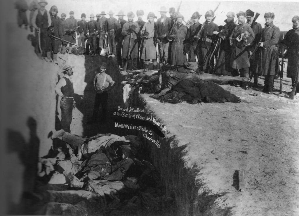 Burial of the dead after the massacre of Wounded Knee. U.S. Soldiers putting Indians in common grave; some corpses are frozen in different positions. South Dakota, 1891. Photo: Library of Congress Prints and Photographs Division, Public Domain.