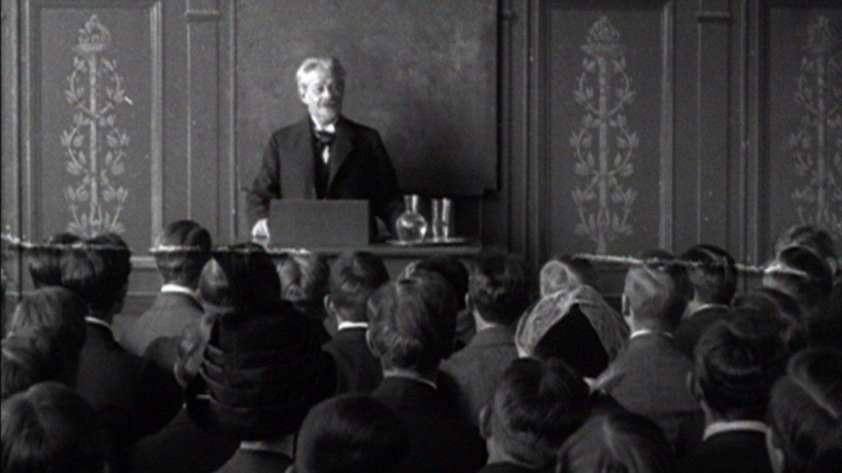 Professor George Brandes (1842-1927) holder forelæsning på Københavns Universitet. De studerende rejser sig høfligt før og efter forelæsningen. Fra en 1 minut lang stumfilm fra 1912.