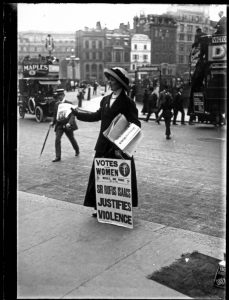 Title: Angleterre Suffragette. The suffragette is selling the 'Votes for Women' newspaper outside Morley's Hotel in Trafalgar Square. The 'Votes for Women' newspaper was one of several suffragette newspapers published during the early years of the 20th century, this particular edition was published on Friday 29th April 1910. 1900-1919. Photo: Ch. Chusseau-Flaviens. George Eastman House Collection. No known copyright restrictions.