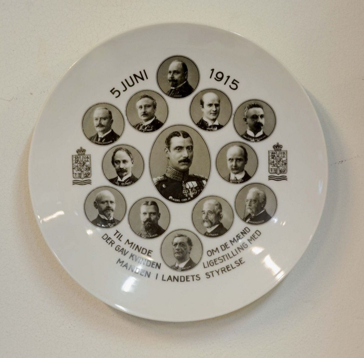 Platte fremstillet af hvidt porcelæn. Platten bærer indskriften: 5 JUNI 1915 TIL MINDE OM DE MÆND DER GAV KVINDEN LIGESTILLING MED MANDEN I LANDETS STYRELSE