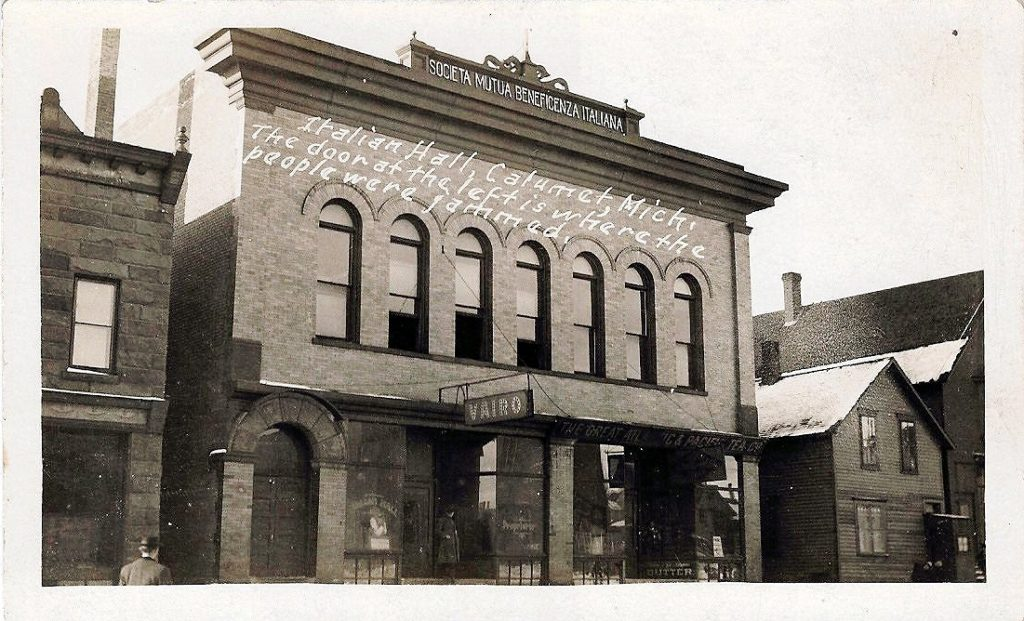 """Italian Hall, Calumet, Michigan, scene of disaster when a crowd upstairs panicked at the (false) cry of """"Fire!"""", December 24, 1913. Seventy-three people (including fifty-nine children) were killed in the crush at the exit. Photo: rppc.(Real photo postcard). (CC BY-SA 2.0)."""