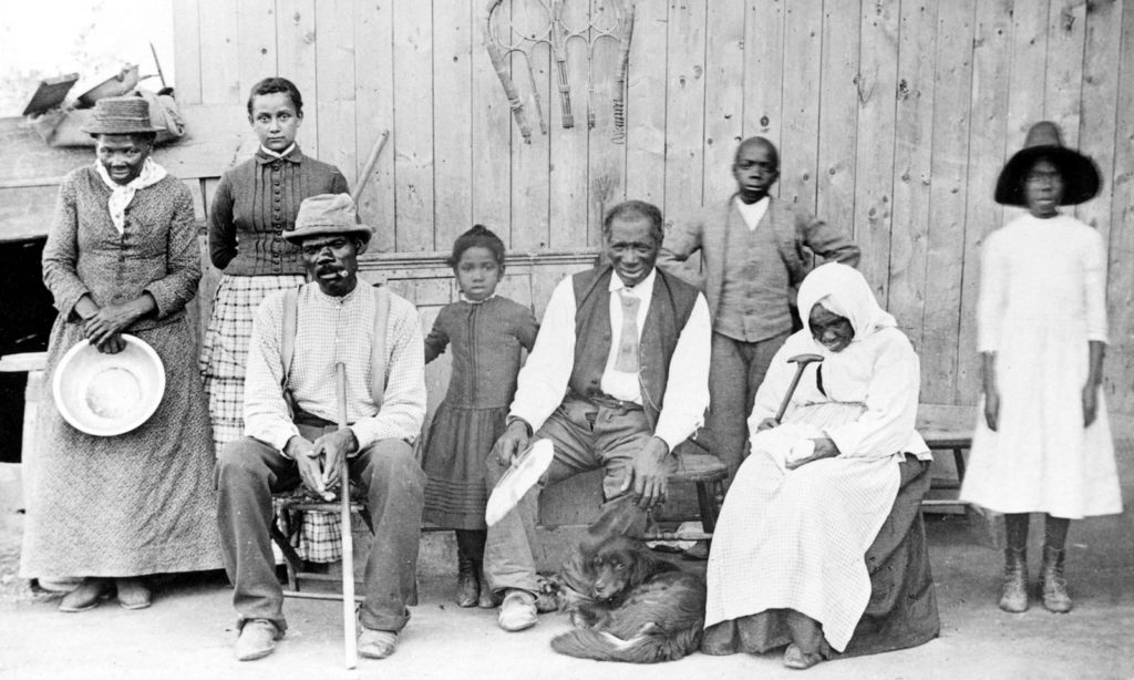 """Harriet Tubman (c. 1820 – March 10, 1913), far left, with family and neighbors, circa 1887, at her home in Auburn, NY. Left to right: Harriet Tubman; Gertie Davis {Watson} (adopted daughter born 1874, died ?) behind Tubman; Nelson Davis (husband and 8th USCT veteran); Lee Chaney (neighbor's child); """"Pop"""" John Alexander (elderly boarder in Tubman's home); Walter Green (neighbor's child); Blind """"Aunty"""" Sarah Parker (elderly boarder); Dora Stewart (great-niece and granddaughter of Tubman's brother Robert Ross aka John Stewart). [Note: Dora Stewart is sometimes cropped out of other versions of this photograph]. Date: Catherine Clinton (2004) gives the date as c. 1885. Source: Bettman/Corbis, through The New York Times photo archive, via their online store, here. Photographer William H. Cheney, South Orange, NJ. Public Domain."""