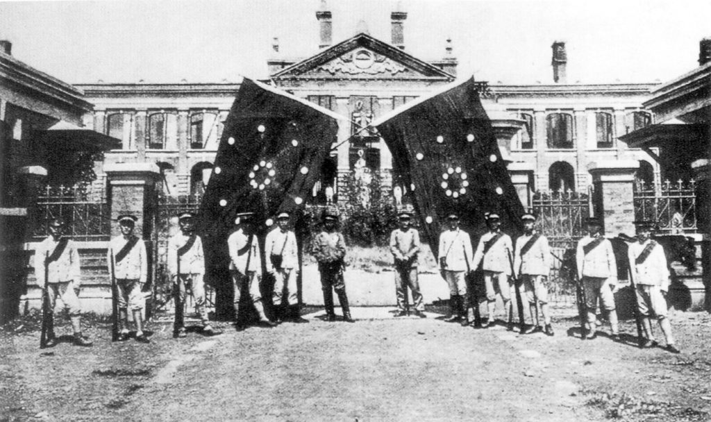 Posing in front of the Hubei Military Government in Wuhan after the en:Wuchang Uprising, with flags of the uprising in the background. Photo circa 1911. Copyright expired. From zh wp. Public Domain.