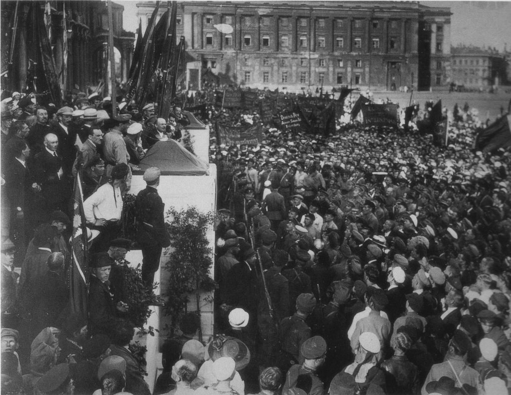 V. I. Lenin making a speech at a meeting dedicated to the laying of the foundation stone for a monument to K. Liebknecht and R. Luxemburg, in Dvorstsovaya Square. Petrograd, 19 July 1920. Photo: Viktor Bulla (1883–1938). Public Domain.