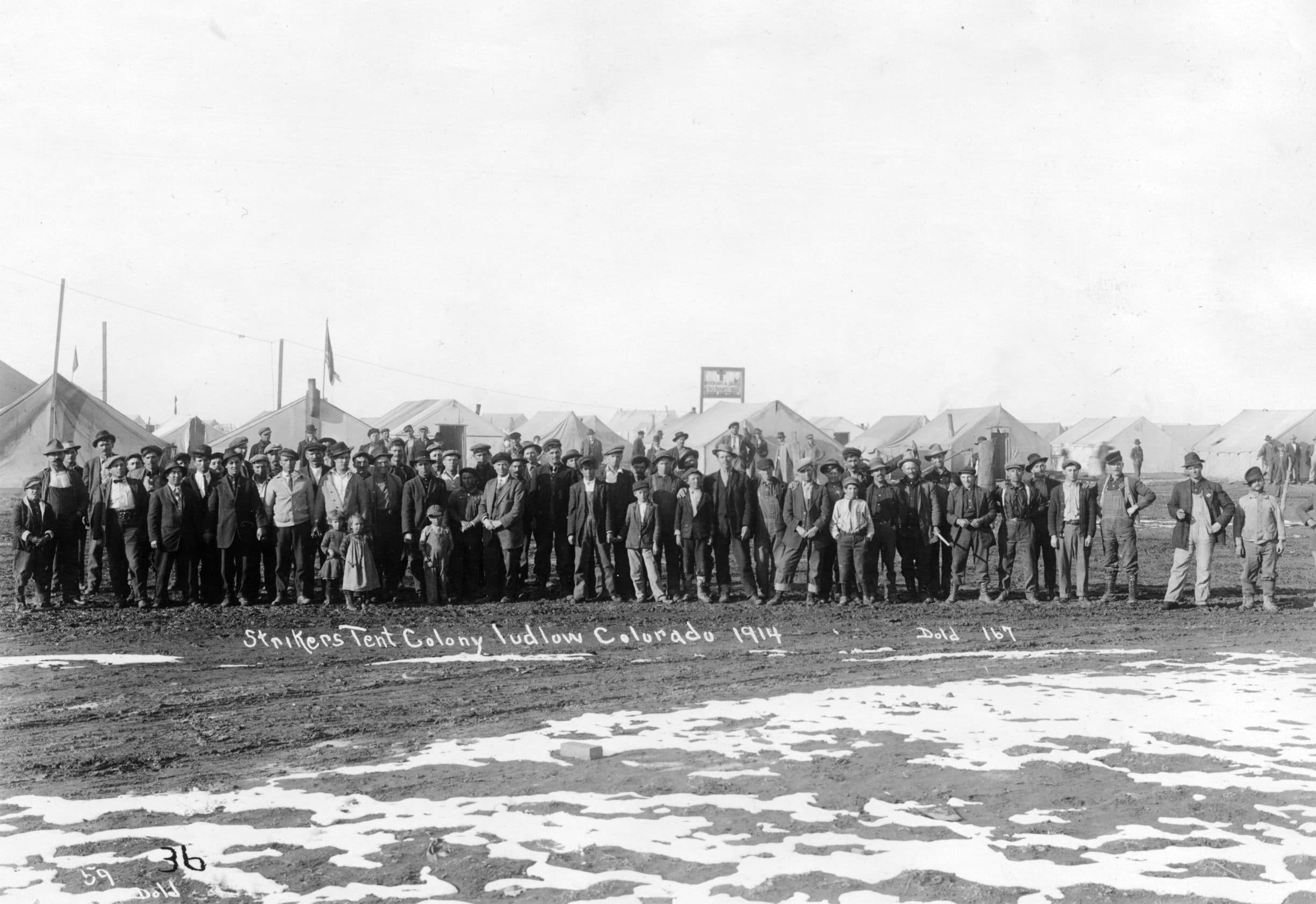 """Portrait of men, boys, and girls at the UMW camp for coal miners on strike against CF&I in Ludlow, Las Animas County, Colorado; sign on canvas tent behind the crowd reads: """"Dispensary and office of Drs. Harvey and Davis Union Doctors."""" Image from 1914. Photo: Dold, Lewis R. Public Domain."""