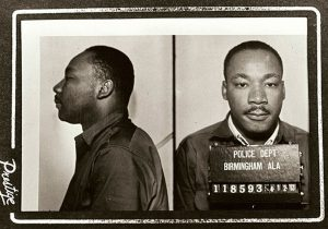 """Mugshot of Martin Luther King Jr following his 1963 arrest in Birmingham. Date: April 1963. Original publication: circulated to news media in April 1963. Author: Birmingham AL police dept, Public Domain. Source: <a href=""""https://commons.wikimedia.org/wiki/File:MLK_mugshot_birmingham.jpg"""">Wikimedia Commons</a>"""