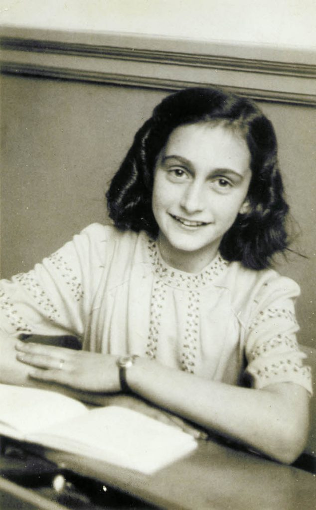 Anne Frank laughing at the school photographer. This photograph was made at the Joods Lyceum (Jewish High School Amsterdam, address Voormalige Stadstimmertuin 1), December 1941. Source: annefrank.org. Author: Anonymous. Public Domain. Source: Wikimedia Commons.
