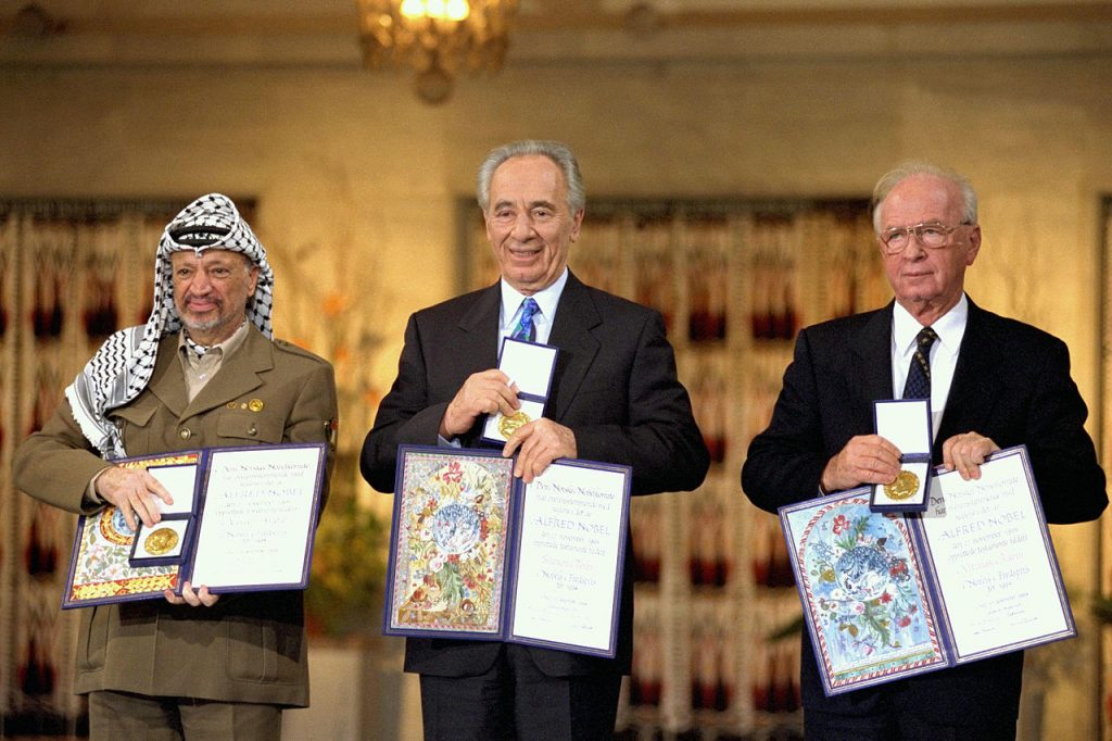 """And still no peace. The Nobel Peace Prize laureates for 1994 in Oslo. From left to right: PLO Chairman Yasser Arafat, Israeli Foreign Minister Shimon Peres, Israeli Prime Minister Yitzhak Rabin. Taken on 10 December 1994. Source: Government Press Office. Author: Saar Yaacov, GPO. (CC BY-SA 3.0). Source: <a href=""""https://commons.wikimedia.org/wiki/File:Flickr_-_Government_Press_Office_(GPO)_-_THE_NOBEL_PEACE_PRIZE_LAUREATES_FOR_1994_IN_OSLO..jpg"""">Wikimedia Commons</a>"""