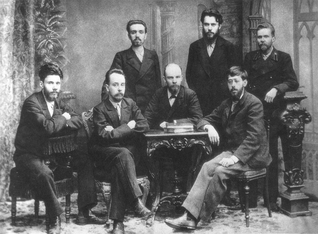 A meeting of the St. Petersburg chapter of the Union of Struggle for the Liberation of the Working Class in February 1897. Shortly after the picture was taken the whole group was arrested by the Okhrana. From left to right (standing) : A.L. Malchenko, P. K. Zaporozhets, Anatoly Vaneyev. (sitting) : Victor V. Starkov, Gleb Krzhizhanovsky, Vladimir Lenin and Julius Martov. Saint Petersburg, February 1897. Photo: Nadezhda Konstantinovna Krupskaya (1869-1939). Public Domain.