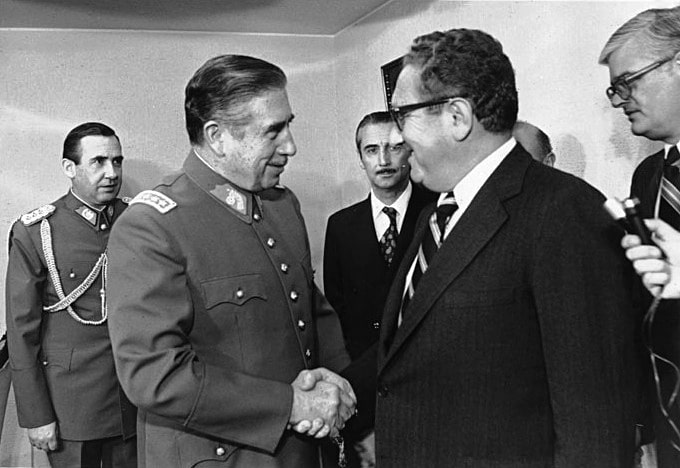 """U.S. Secretary of State Henry Kissinger with Pinochet in 1976. Source: Archivo General Histórico del Ministerio de Relaciones Exteriores ([1]). Author: Ministerio de Relaciones Exteriores de Chile. (CC BY 2.0 CL). Source: <a href=""""https://commons.wikimedia.org/wiki/File:Reuni%C3%B3n_Pinochet_-_Kissinger.jpg"""">Wikimedia Commons</a>"""