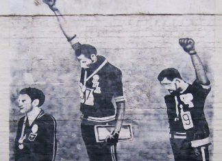 Graffiti on house wall in Newtown, Australia - The house might be demolished now. Tommie Smith (center) and John Carlos (right) showing the raised fist on the podium after the 200m in the 1968 Summer Olympics. Silver medallist Peter Norman from Australia (left) joins them in wearing Olympic Project for Human Rights badges. Photo: Taken on August 2, 2010 by Newtown grafitti. (CC BY 2.0).