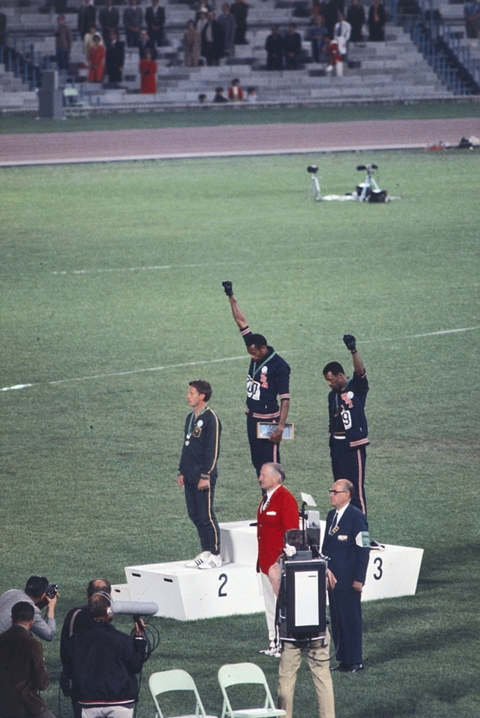 American sprinters Tommie Smith and John Carlos, along with Australian Peter Norman, during the award ceremony of the 200 m race at the Mexican Olympic games. During the awards ceremony, Smith (center) and Carlos protested against racial discrimination: they went barefoot on the podium and listened to their anthem bowing their heads and raising a fist with a black glove. Mexico City, Mexico, 16 October 1968. Photo: Angelo Cozzi (Mondadori Publishers). Public Domain.