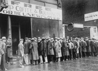 """Unemployed men queued outside a depression soup kitchen opened in Chicago by Al Capone. The storefront sign reads """"Free Soup Coffee & Doughnuts for the Unemployed."""" February 1931. Photo: Unknown author or not provided. Current location: National Archives at College Park, National Archives and Records Administration. Public Domain."""