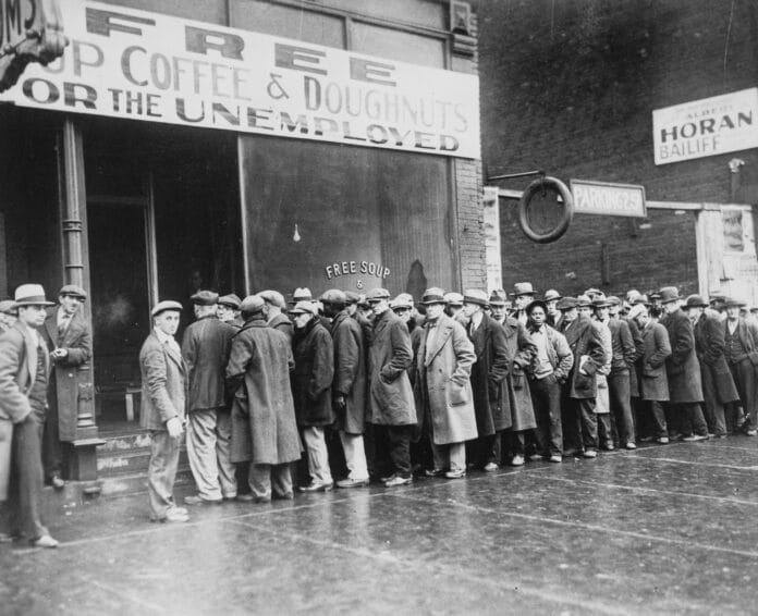 Unemployed men queued outside a depression soup kitchen opened in Chicago by Al Capone. The storefront sign reads