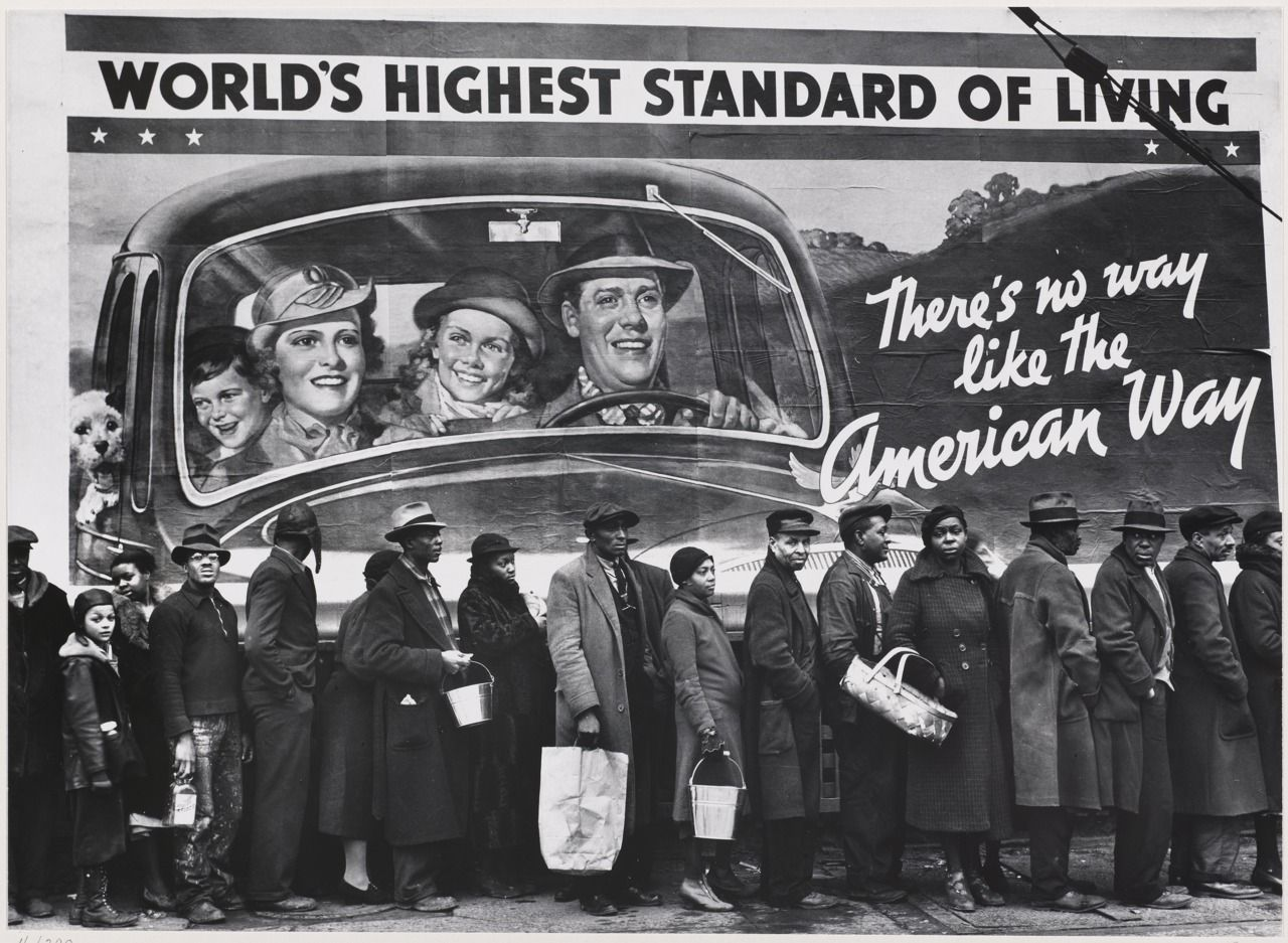 Reallity meets the American dream. Queue of black residents of Louisville KY waiting for distribution of relief supplies during the 1937 Ohio River flood. Photo: Margaret Bourke-White, the first female photographer for Life/Time, captured iconic images that painted a vast global political and socioeconomic landscape. Public Domain.