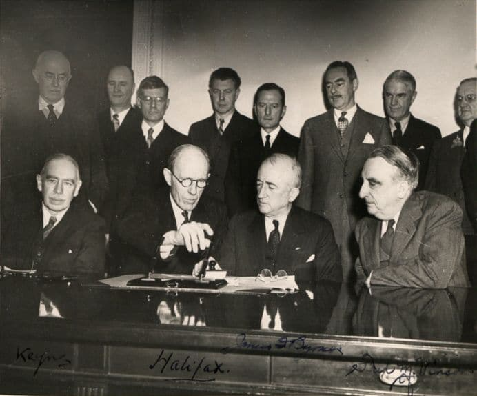 Photograph of the signing of the Anglo-American loan agreement at the State Dept, Washington, on 6 Dec. 1945. Sitted from left to right: John Maynard Keynes, Lord Halifax, James Byrnes, Fred Vinson. Photo: The National Archives UK. Collection: Part of the Colonial Office photographic collection held at The National Archives. Public Domain.