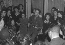"Pete Seeger, noted folk singer, leading the crowd in ""When We March into Berlin"" at the opening of the Washington labor canteen, sponsored by the United Federal Workers of American, Congress of Industrial Organizations (CIO) CREATED/PUBLISHED: 1944 Feb. Photo: Joseph A. Horne (Joseph Anthony), photographer. Source: Library of Congress Prints and Photographs Division Washington, D.C. Public Domain."