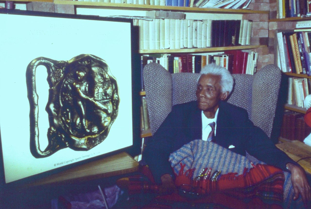C.L.R. James viewing an enlargement of the Barbados Cricket Buckle at his home in Brixton, London. 1988. Foto: Hill123.