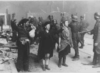 """The original caption of the Nazi: """"These bandits offered armed resistance"""". Picture taken at Nowolipie street looking East, near intersection with Smocza street. In the back one can see ghetto wall with a gate, between 19 April 1943 and 16 May 1943. Photo: Unknown author (Franz Konrad confessed to taking some of the photographs, the rest was probably taken by photographers from Propaganda Kompanie nr 689. Collection: Bildarchiv Preussischer Kulturbesitz (BPK). Public Domain."""