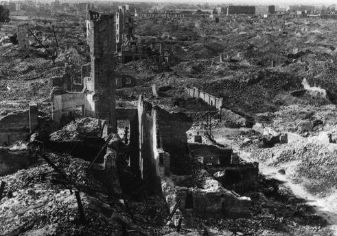 Warsaw Ghetto, smashed into the ground by German destroying forces (de.: Vernichtungskommando), according to Adolf Hitler`s order, after supressing of the Warsaw Ghetto Uprising in 1943. North view from Courthouse at Leszno street, in the foreground is seen the ruins of houses: Leszno 52 and 50, photo taken in 1945. Photo: Unknown. Public Domain.
