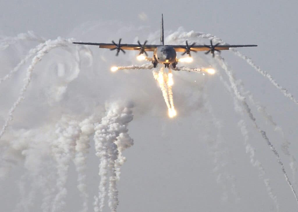 A British C-130J Hercules aircraft launches defensive countermeasures prior to being the first coalition aircraft to land on the newly reopened military runway at Baghdad International Airport, 1 July 2003. Photo: Master Sergeant Robert R. Hargreaves Jr. Public Domain.