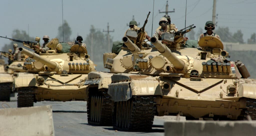 Iraqi tanks assigned to the Iraqi Army 9th Mechanized Division drive through a checkpoint near Forward Operating Base Camp Taji, Iraq. Photo: Taken on 18 May 2006 by U.S. Navy photo by Photographer's Mate 1st Class Michael Larson (RELEASED). Public Domain.