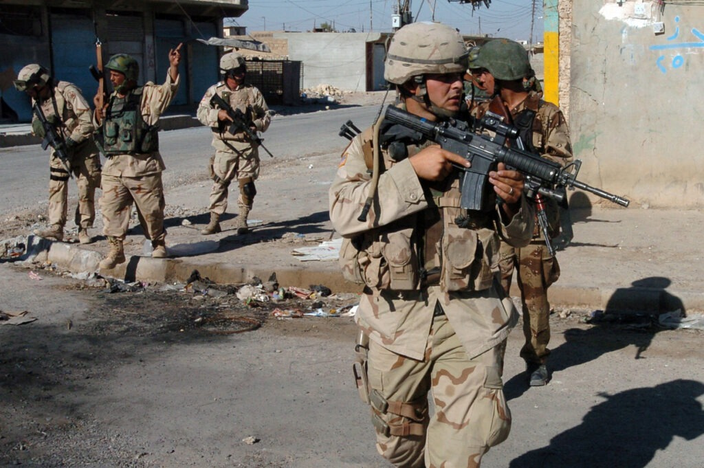 U.S. Army and Iraqi soldiers cross an intersection during a routine security patrol in downtown Tal Afar, Iraq, on Sept. 11, 2005. Iraqi army security forces, with assistance from the 3rd Armored Cavalry Regiment, are providing security for the region of Tal Afar in order to disrupt insurgent safe havens and to clear weapons cache sights in the area of operation. Photo: Petty Officer 1st Class Alan D. Monyelle, U.S. Navy. Public Domain.