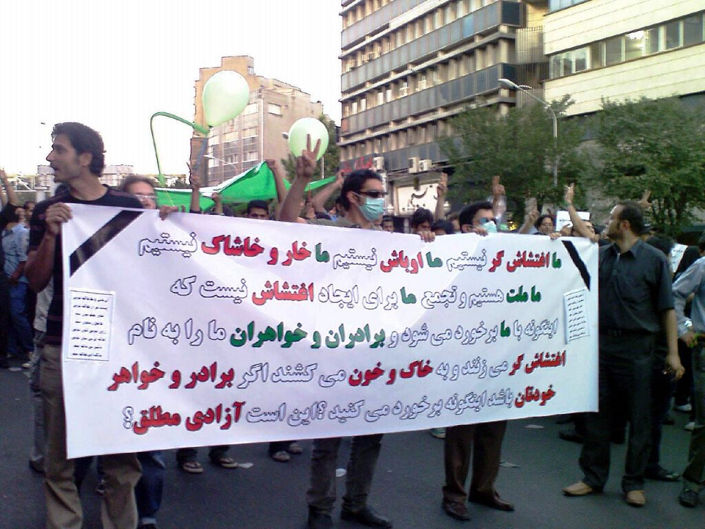 """Protest demonstration against election results, 7th Tir thru Karimkhan to Vali Asr Sq. and beyond, Tehran. banner reads: """"We are not rioters. We are not hooligans. We are not twigs and splinters. We are the people, and we have not gathered here to riot, even though youve treated us like rioters, beating and killing our brothers and sisters in their own blood. Would you dare do the same if it were your own brothers and sisters? Is this the absolute freedom[1] you talk of?"""" Twigs and splinters refers to what Ahmadinejad called the defeated Mousavi supporters in mockery. Author: Saba. Public Domain. Source: <a href=""""https://commons.wikimedia.org/wiki/File:Tazahorat_sabz_(27).JPG"""">Wikimedia Commons</a>"""