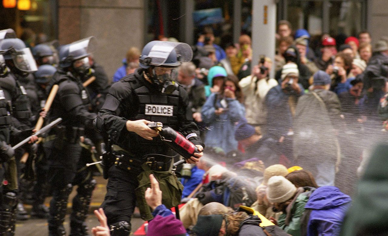 WTO protests in Seattle, November 30, 1999. Pepper spray is applied to the crowd. Source: WTO protests 10. Author: Steve Kaiser from Seattle, US. (CC BY-SA 2.0). Source: Wikimedia Commons.
