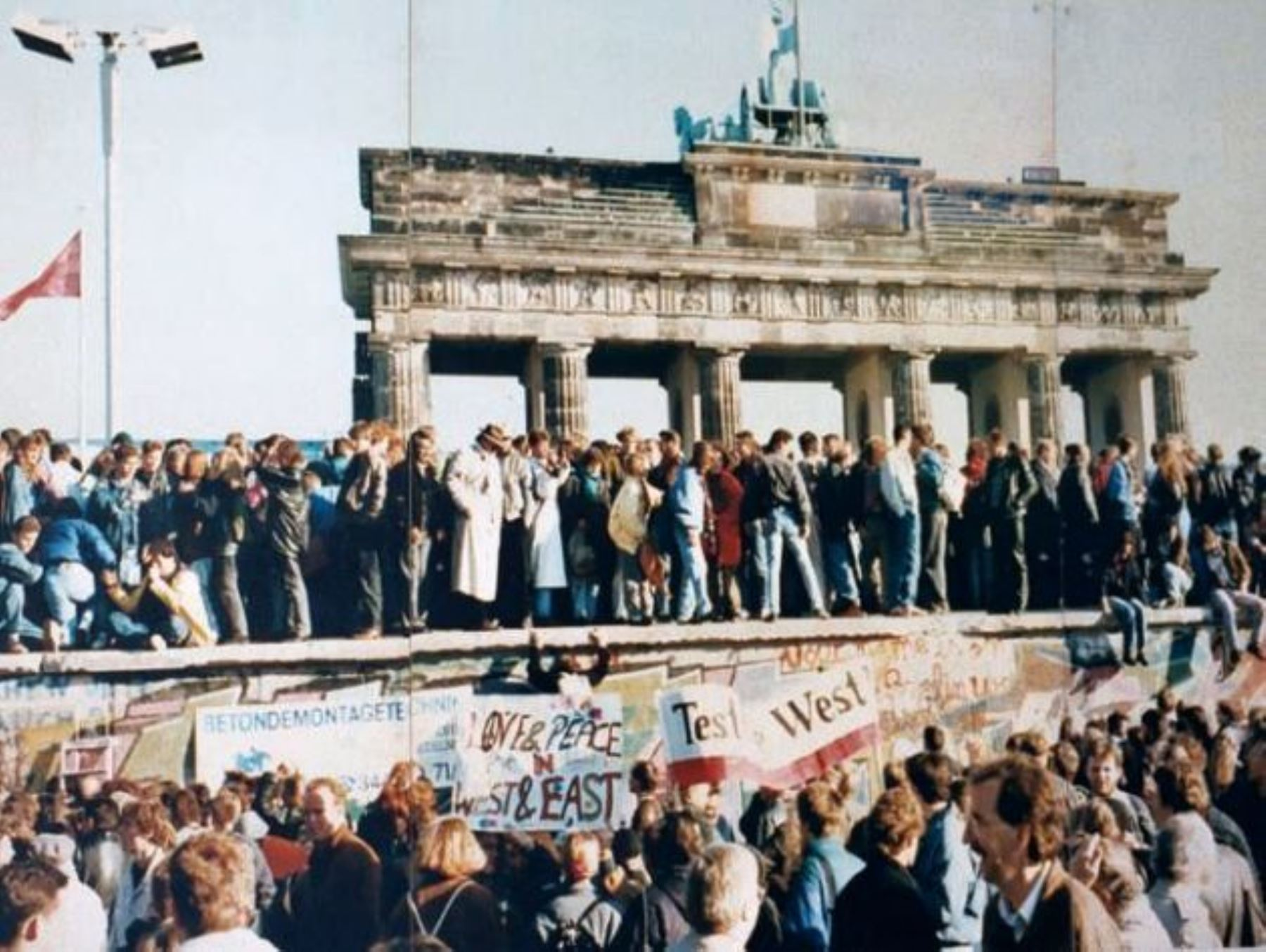 The Fall of the Berlin Wall, 1989. The photo shows a part of a public photo documentation wall at the Brandenburg Gate, Berlin. The photo documentation is permanently placed in the public. Photo: Original photo taken 9 November 1989 by unknown author. Reproduction from public documentation/memorial by Lear 21 at English Wikipedia. (CC BY-SA 3.0).