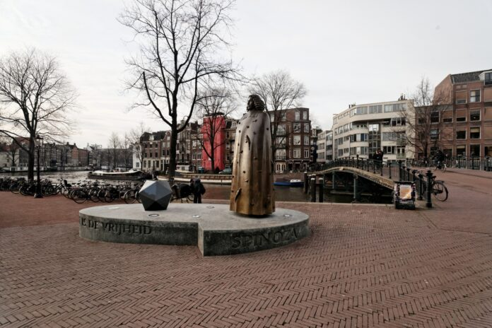 Amsterdam - Zwanenburgwal / Amstel - View West on Statue of Benedictus de Spinoza. Statue made 2008 by Nicolaas Lambertus Maria (Nicolas) Dings (1953-), Dutch sculptor and draughtsman. Photo: Taken 2008 by Txllxt TxllxT. (CC BY-SA 4.0).