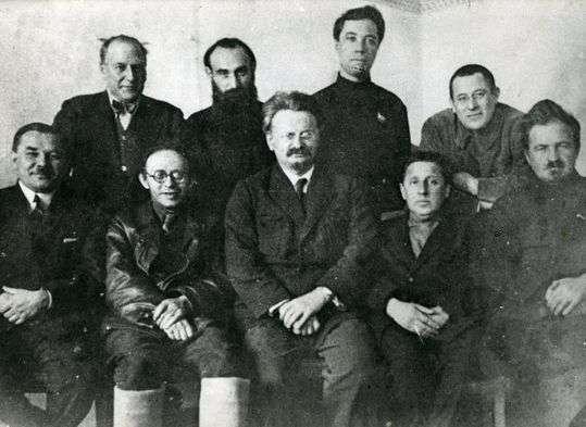 """Ledere af den trotskistiske """"Venstre Opposition"""" i 1927 kort før deres udvisning fra Moskva. Set fra venstre mod højre: L. Serebryakov, K. Radek, L. Trotsky, M. Boguslavsky og E. Preobrazhensky; stand: H. Rakovsky, J. Drobnis, A. Beloborodov og L. Sosnovsky. Public Domain."""