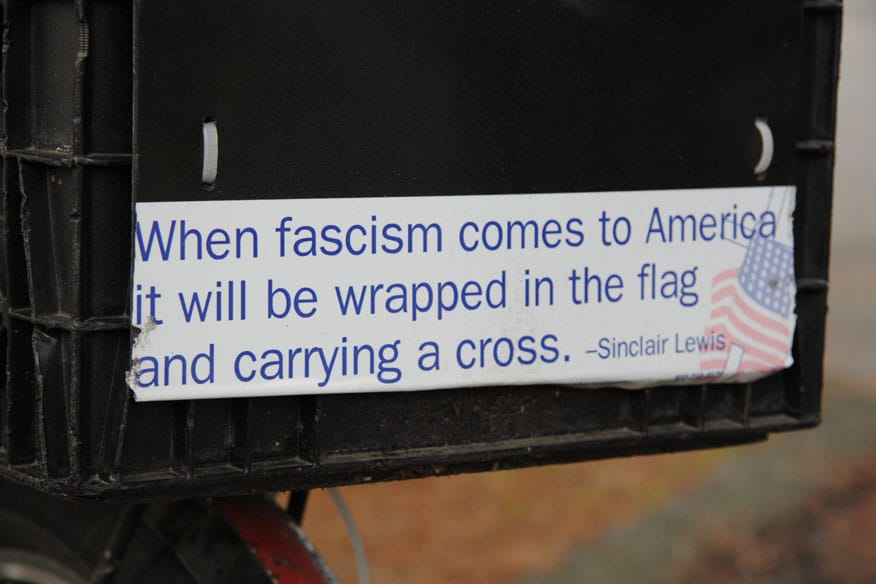 """Closeup of bumper sticker with famous Sinclair Lewis line """"When fascism comes to America it will be wrapped in the flag and carrying a cross"""" This quote is often attributed to Sinclair Lewis but has not been verified. The Sinclair Lewis Society notes the following: This quote sounds like something Sinclair Lewis might have said or written, but we've never been able to find this exact quote. Date: 27 November 2008. Photo: Robert F. W. Whitlock from Olympia, Washington. (CC BY 2.0)."""