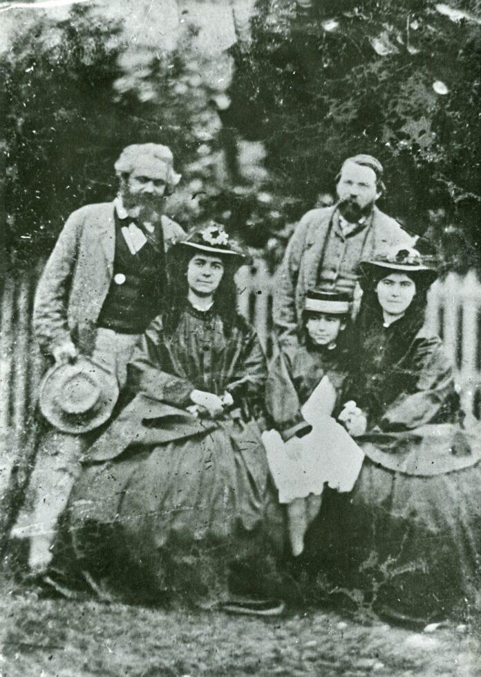 Friedrich Engels, Karl Marx and Marx's daughters: Jenny Caroline (1844–1883), Jenny Julia Eleanor (1855–1898), and Jenny Laura (1845–1911). Date: 1860s (1864?). Photo: Unknown. Public Domain.