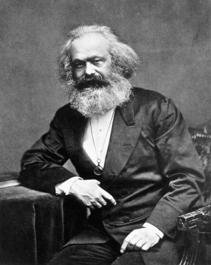 Photographic portrait of Karl Marx seated with a thumb in his lapel and his hand on his thigh, 1875. From: Reminiscences of Carl Schurz, Vol. I, New York: McClure Publ. Co., 1907, Chap. 4, facing p. 170. (This is the source of the first version only. Photo: John Jabez Edwin Mayal (1813–1901). Public Domain.