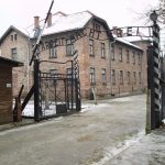 """The """"Arbeit macht frei"""" sign at the main gate of the Auschwitz I concentration camp in German-occupied Poland. Photo: Taken 27 November 2005 by Tulio Bertorini. (CC BY-SA 2.0)."""