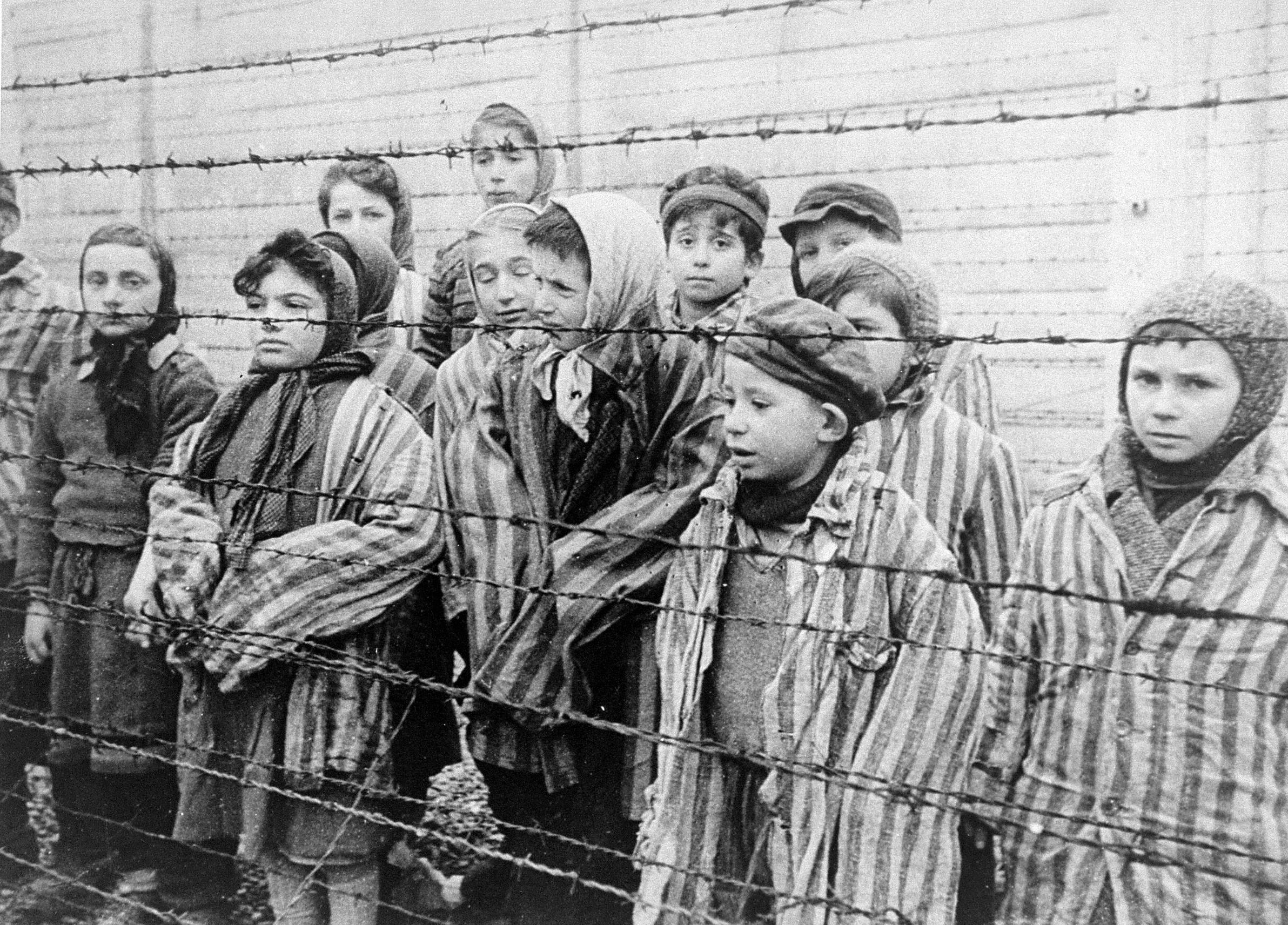 Still photograph from the Soviet Film of the liberation of Auschwitz, taken by the film unit of the First Ukrainian Front, shot over a period of several months beginning on January 27, 1945 by Alexander Voronzow and others in his group, ordered by Mikhael Oschurkow, head of the photography unit. Child survivors of Auschwitz, wearing adult-size prisoner jackets, stand behind a barbed wire fence. Collection: USHMM/Belarusian State Archive of Documentary Film and Photography, USA. Public Domain.