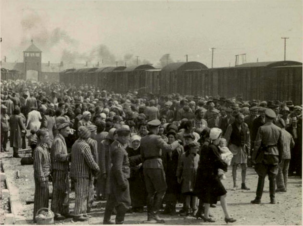 """Selection"" of Hungarian Jews on the ramp at Auschwitz-II (Birkenau), Poland during the German occupation, May/June 1944. Jews were sent either to work or to the gas chamber. The photograph is part of the collection known as the Auschwitz Album. The collection as a whole was first published as The Auschwitz Album in 1980 in the United States, Canada and elsewhere, by the Nazi hunter Serge Klarsfeld, but individual images had been published before that – for example, during the 1947 Auschwitz trial in Poland and the 1963–1965 Frankfurt Auschwitz trials. Photo: Unknown. Several sources believe the photographer to have been Ernst Hoffmann or Bernhard Walter of the SS. Public Domain."