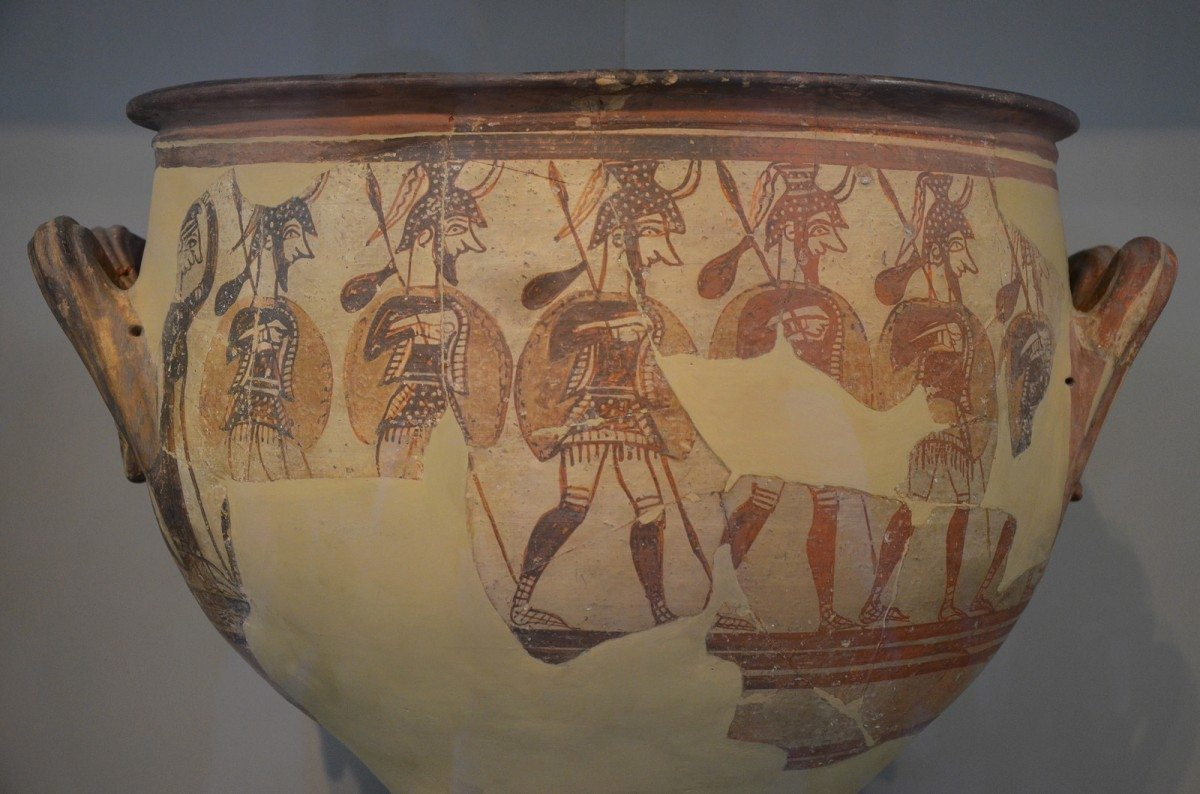 Mycenae, Warrior's Vase, Helladic Period/Civilization. Large krater depicting men in full armour as they depart for war, a sack of supplies hanging from their spears, to the side a woman raises her hand in a farewell gesture, from Mycenae Acropolis, 12th century BC. Collection: National Archaeological Museum of Athens. Photo: Taken on April 18, 2014 by Carole Raddato. (CC BY-SA 2.0).