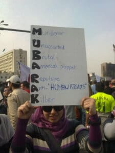 A young woman carrying a card during the 2011 Egyptian Revolution in El Tahrir Square. Photo: Taken 1 February 2011 by Essam Sharaf. (CC BY-SA 3.0).