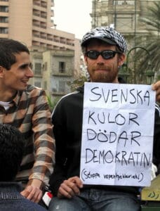 """A Swede who joined the 2011 Egyptian protests in Tahrir Square. The text reads: """"Swedish bullets kill democracy (stop arms hypocrisy!)"""", in reference to the use by Egyptian riot police and security forces of ammunition made in Sweden. Photo: Taken 6 February 2011 by Sherif9282. (CC BY-SA 3.0)."""