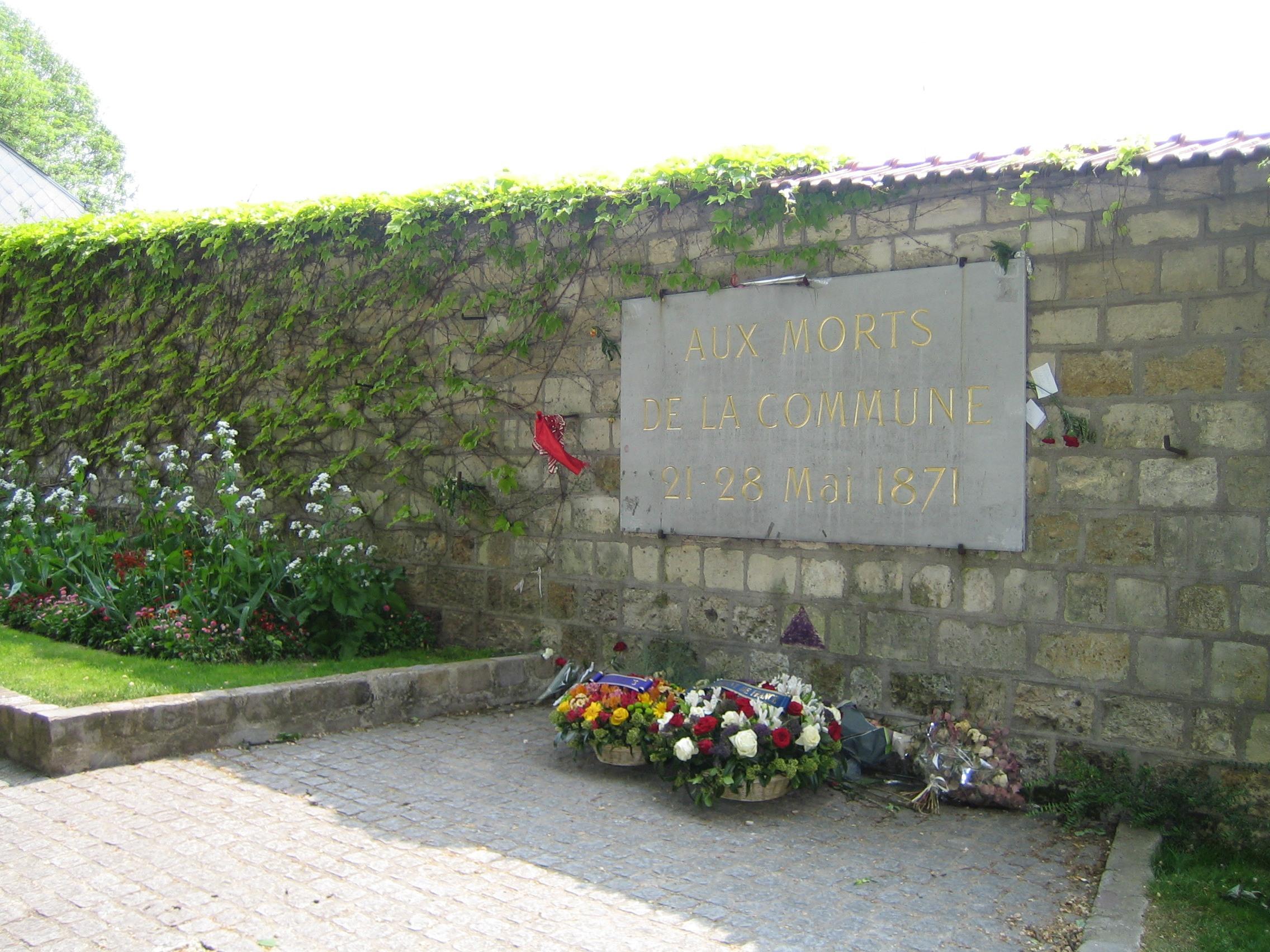 """Kommunardernes Mur, Le mur des Fédérés på Päre-Lachaise Kirkegård i Paris, hvor kommunarderne blev trængt sammen og skudt ned. (Wikipedia.org). Tekst på mindeplade: """"Til Kommunens døde 21 - 28 maj 1871"""". Siden samlende optogs-sted (som Fælledparken i Kbh.) for den franske venstrefløj. Foto: Taget 8. maj, 2010 af Ade46. (CC BY-NC-ND 2.0)."""