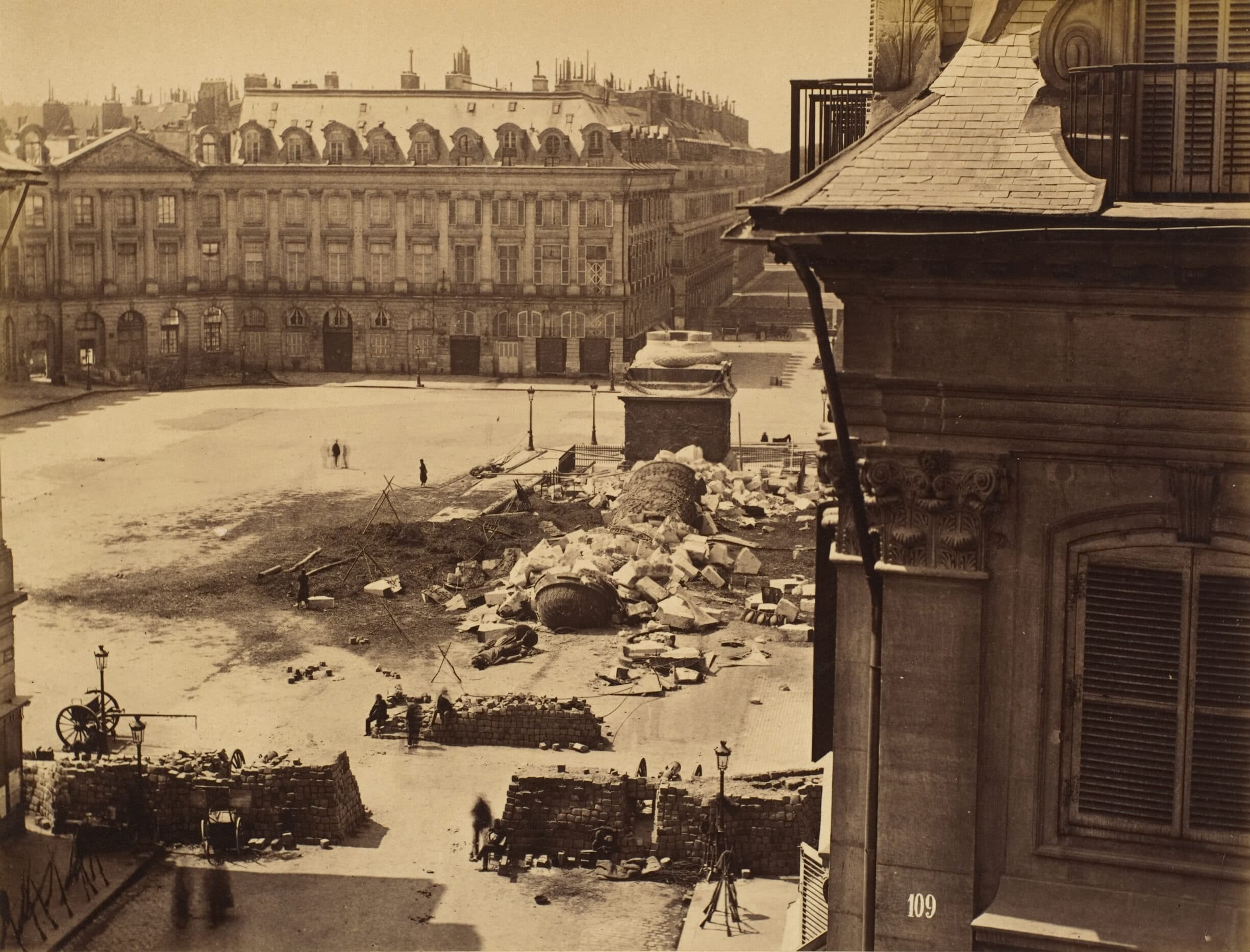 On May 16, 1871, a group of Communards pulled down the Vendôme Column. In Franck's photograph its shattered remains litter the Place Vendôme. Modeled on the ancient Column of Trajan in Rome, the Vendôme Column was built by Napoleon I in the first decade of the nineteenth century as a glorification of the victorious French soldiers who defeated the Russian-Austrian alliance at the Battle of Austerlitz; the seventy-six battle-scene bas-reliefs that spiral up the shaft were cast from the bronze of 250 captured Russian cannons. Louis-Philippe crowned the column with a statue of Napoleon in 1833, and Napoleon III replaced it thirty years later with another of Napoleon in Roman costume. Photo: Albumen silver print from glass negative by François-Marie-Louis-Alexandre Gobinet de Villecholle Franck (1816–1906), French photographer. Collection: Metropolitan Museum of Art, New York. Public Domain.