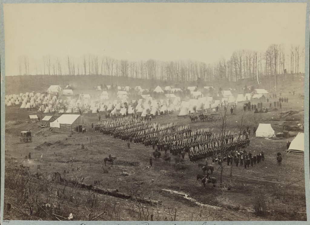 Camp of 36th Pennsylvania Infantry. Military band, troops on the field, officers on horseback, and tents in the background. Photo: Taken between 1861 and 1865. Collection: Civil War Photograph. the United States Library of Congress's Prints and Photographs division. Public Domain.