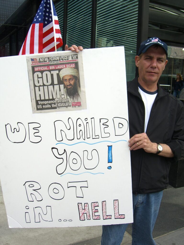 Joy over the death of Osama Bin Laden. A sign holder in front of the Millenium Hilton Hotel on Church Street in Manhattan, which faces the World Trade Center site, on May 2, 2011, reacting to the death of Osama bin Laden, which was announced the night before. Photo: Luigi Novi. (CC BY 3.0).