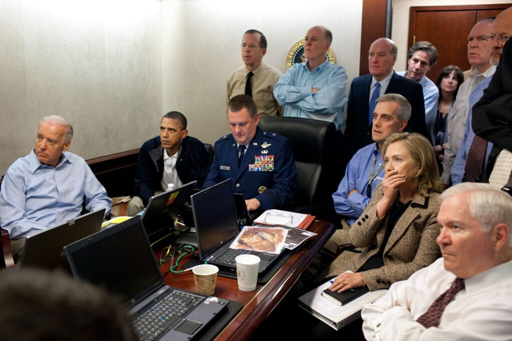 The Situation Room. U.S. President Barack Obama and Vice President Joe Biden, Hillary Clinton along with members of the national security team, receive an update on Operation Neptune Spear, a mission against Osama bin Laden, in one of the conference rooms of the Situation Room of the White House, May 1, 2011. They are watching live feed from drones operating over the bin Laden complex. Photo: taken 1 May 2011 by Peter Souza, (1954-), Official White House Photographer. Public Domain.