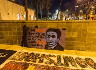 "Banner outside the Minneapolis Police Department fourth precinct, Plymouth Avenue, following the officer-involved shooting of Jamar Clark on November 15, 2015. The quote says: ""We revolt simply because for many reasons we can no longer breathe."" -Frantz Fanon. Photo by Tony Webster. (CC BY 2.0)."